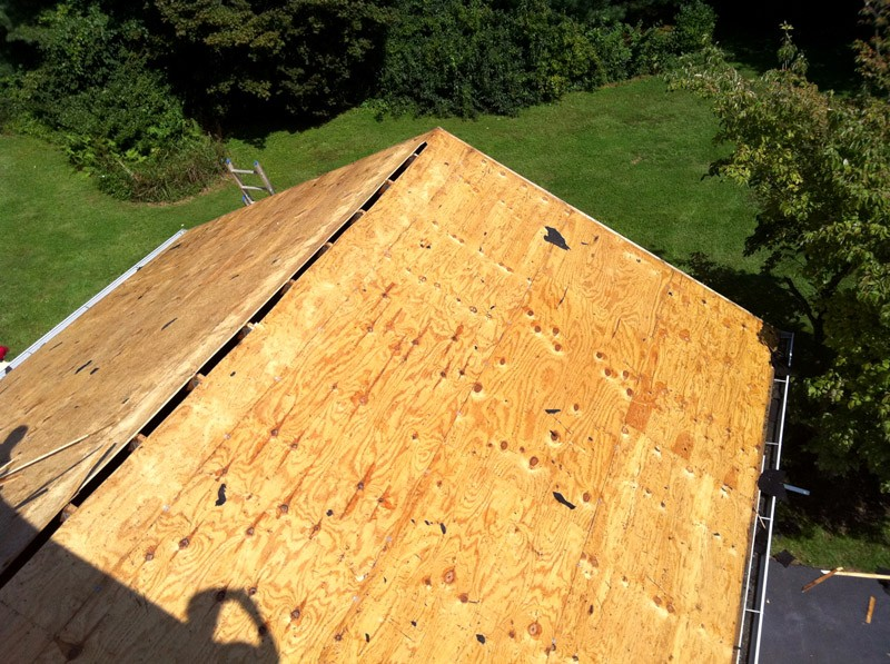 Inspecting wood decking - shingle roofing installation in Newark DE.